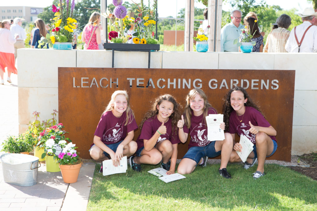 Children posing in front of the Leach Teaching Gardens sign.